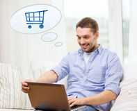 Smiling man with laptop shopping online at home Royalty Free Stock Images