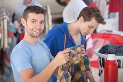 Smiling Man In Laundromat. Smiling Caucasian man holds plaid shirt in laundromat royalty free stock photos