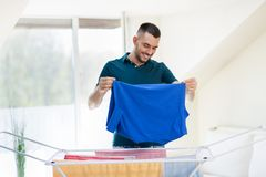 Smiling man with laundry and drying rack at home Royalty Free Stock Images