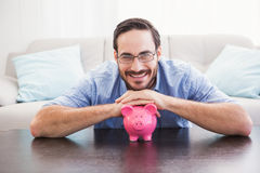 Smiling man laying on the piggy bank Royalty Free Stock Images