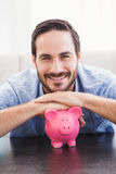 Smiling man laying on the piggy bank Stock Image