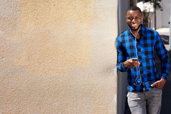 Smiling man leaning against wall with smart phone and earphones Royalty Free Stock Photo