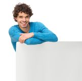 Smiling Man Leaning on Blank Signboard. Isolated on white background royalty free stock image