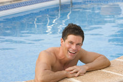 Smiling man leaning on edge of swimming pool.  royalty free stock photography