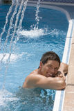Smiling man leaning on edge of swimming pool Royalty Free Stock Photo