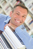 Smiling man leaning on stack books Royalty Free Stock Image