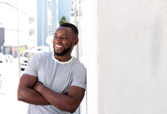 Smiling man leaning on wall outside in city Royalty Free Stock Images