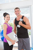 Smiling man lifting dumbbell with trainer Royalty Free Stock Image