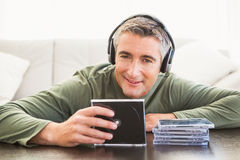 Smiling man listening music and holding cd Stock Images