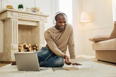 Smiling man listening to music. Listening to music. Attractive happy smiling afro-american man listening to music while sitting on the floor with his laptop and Royalty Free Stock Photo
