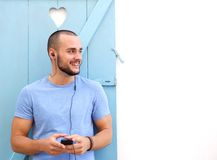 Smiling man listening to music on mobile phone with earphones Royalty Free Stock Photo