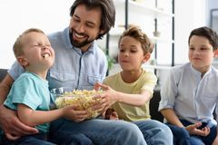 Smiling man and little sons eating popcorn while watching film together. At home stock image