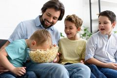 Smiling man and little sons eating popcorn while watching film together. At home royalty free stock image