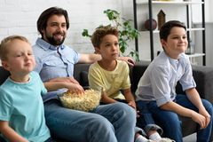 Smiling man and little sons with popcorn watching film together. At home royalty free stock images