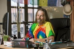 Smiling Man with Long Hair in a Colorful Office. Smiling man in tie dye shirt at his desk Stock Photo