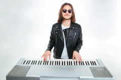 Smiling man with long hair in sunglasses playing on synthesizer. Smiling attractive young man with long hair in sunglasses playing on synthesizer over white stock photo
