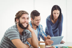 Smiling man looking away with coworkers using digital tablet Royalty Free Stock Photo