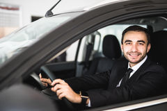 Smiling man looking from a car window Royalty Free Stock Photos