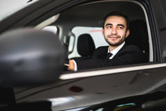 Smiling man looking from a car window Royalty Free Stock Photo