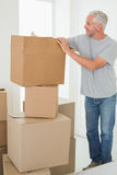Smiling man looking at cardboard moving boxes Royalty Free Stock Images