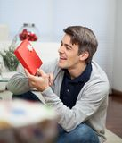 Smiling Man Looking At Christmas Gift Royalty Free Stock Images