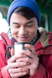 Smiling man looking at coffee in insulated drink container during winter Stock Photography