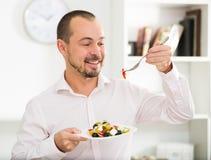 Smiling man looking at greek salad Stock Photography