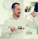 Smiling man looking at greek salad Stock Image