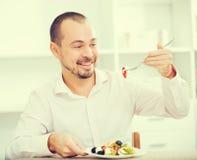 Smiling man looking at greek salad Stock Images