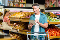 Smiling man looking at the grocery list Stock Image