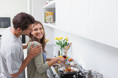 Smiling man looking at his wife who is cooking vegetables Royalty Free Stock Images