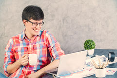 Smiling man looking at laptop. Smiling caucasian male with coffee sitting at wooden office table with various items looking at laptop screen Stock Photo