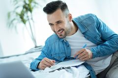 Smiling man looking at laptop while taking notes. Interesting information. Joyful millennial guy grinning broadly while sitting at a bed and writing something Royalty Free Stock Images