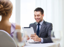 Smiling man looking at menu on tablet pc computer Stock Photo