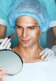 Smiling man looking in the mirror before surgery plastic surgery. Stock Images