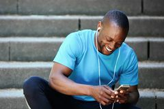 Smiling man looking at mobile phone and listening to music Stock Images