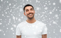 Smiling man looking up over snow background. Winter, christmas, idea, inspiration and people concept - happy smiling young man looking up over snow on gray Stock Images