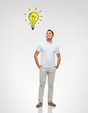 Smiling man looking up to lighting bulb Royalty Free Stock Image