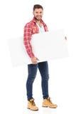 Smiling man in lumberjack shirt holding blank placard Stock Photos