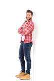 Smiling man in lumberjack shirt leaning on the white wall Stock Photos