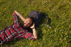 Smiling man lying on backpack. Cheerful hipster tourist man lying on grass with backpack under head Royalty Free Stock Photo