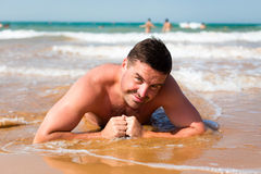 Smiling man lying on a beach against the sea. Smiling man lying on the beach against the sea Stock Photo