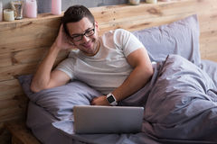 Smiling man lying in a bed with his laptop Royalty Free Stock Photo