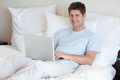 Smiling man lying in bed with laptop Stock Images