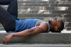 Smiling man lying down on back outside Stock Image