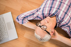 Smiling man lying on floor next to laptop Stock Photos