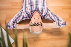 Smiling man lying on floor next to laptop Royalty Free Stock Images