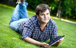 Smiling man lying on grass at park and using digital tablet Stock Photo