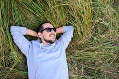 Smiling man lying on the grass Royalty Free Stock Images
