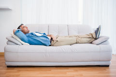 Smiling man lying and relaxing on the couch Stock Image